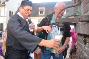 Ron Hermus laat als pastoor Jos Janssen een groot glas vollopen met Reuzenbier. Rechts Ad Kocx, een van de vrijwilligers die de pomp heeft gerestaureerd en vernieuwd.(Foto: Paul Spapens)