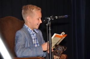 Kleinzoon Luca van Laarhoven van Martien Oerlemans leest tijdens de culturele avond van WieKentKunst voor uit het dierenboek 'Jakkes'. Op zijn schoot het gezinshondje Bingo. Het voorlezen van kleinzoon Luca werd gebruikt als middel om de winnaar van de Moergestelse vrijwilligersprijs naar Den Boogaard te lokken.(Foto: Hennie van Schooten)