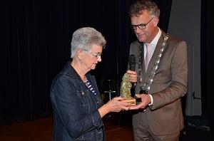 Uit handen van burgemeester Hans Janssen ontvangt Elly van zon het bronzen beeldje van reuzin Ermelindis.(Foto: Paul Spapens)