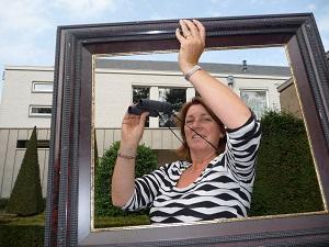 Joke van Dal met verrekijker, ingelijst om het glaskunstwerk achter het raam achter haar te kunnen bekijken.(Foto: Paul Spapens)