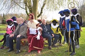 De Sint probeert de nieuw bank uit nadat hij deze met hulp van zijn Zwarte Pieten heeft onthuld. (Foto: Hennie van Schooten)